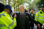 A climate change protester is searched by the police in Millbank on 8th October, 2019 in London, Untited Kingdom. Extinction Rebellion plan to occupy 12 sites situated around key Government locations around Westminster for two weeks to protest against climate change.