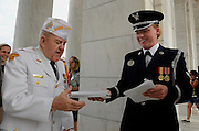 ARLINGTON, VA - May 25, 2009:  U.S. Air Force Honor Guard, Airman 1st Class Teri Groves of Dubois, Pa., hands retired U.S. Navy Chief Petty Officer Neil Kosk of Dundalk, Md., a program in honor of the National Memorial Day Observance in Arlington National Cemetery, which is held on the last Monday in May.  Photo by Johnny Bivera
