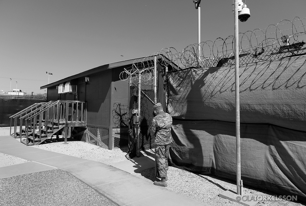 """A military guard at the prison camp at Guantanamo, Cuba, Jan 28 2017, guards a gate at the prison facility.<br /> The guards turn away their faces so you cannot identify them. It is standard operation procedure when pictures are made. When you work as a journalist at the Guantanamo you work under military censorship and all your material is checked every day and approved for publication.<br /> The prison camp on the Guantánamo naval base was the creation of President George W. Bush. The prison camp was considered an important part of the US war on terrorism. Over the years, 779 people have been brought to the camp. 41 people are still detained. Of them, 26 people count as """"forever prisoners"""", indefinite detainees under the Law of War. Two prisoners have been in the camp since it was opened in January 2002. The last prisoner taken to the camp came in March 2008. The so-called war on Terror and the Guantanamo prison camp have been heavily criticized for violation of human rights regarding torture and habeas corpus.<br /> It is unclear what US President Donald Trump wants to do with the camp, but during the election campaign he said that he would fill Guantánamo Bay with """"bad dudes"""". Photo by Ola Torkelsson<br /> Copyright Ola Torkelsson ©"""