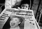 """""""First ladies."""" A six month-old infant girl has a shocked look on her face as she plays with a copy of the broadsheet Guardian newspaper whose front page headline photograph is of Hilary Clinton, then First Lady of the United States. Clinton is also looking aghast at something she is experiencing. Coincidentally, the President's wife and the first-born of this family are both first ladies. The child has sunk down into her high-chair, reacting to something her mother has said. This is from a documentary series of pictures about the first year of the photographer's first child Ella. Accompanied by personal reflections and references from various nursery rhymes, this work describes his wife Lynda's journey from expectant to actual motherhood and for Ella - from new-born to one year-old."""