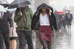 © Licensed to London News Pictures. 08/10/2014. London, UK. Commuters and City workers with umbrellas are caught in heavy rain as they cross London Bridge in central London this morning. Photo credit : Vickie Flores/LNP