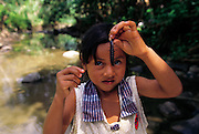 A rural Peruvian girl displays her catch of a chanchu chanchu (Megaloptera Corydyalus armatus Hagen) river insects. The insects are pulled from the undersides of river rocks near the Yanatile River, Koribeni, Peru. (Man Eating Bugs page 157)