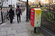 Muslim woman wearing a hijab walks past a Royal Mail post box on a street corner in Whitechapel, London, UK.