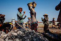 Burmese workers load stones onto a boat for transport south in Mandalay, Myanmar.