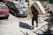 A fireman are taking families good from the destroyed houses.