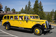 Historic tour bus in front of the Old Faithful Inn, Yellowstone National Park, Wyoming.