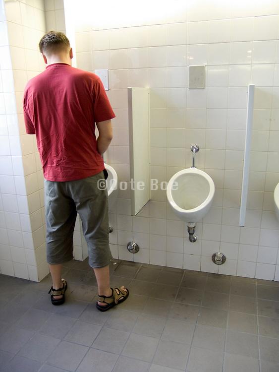 Man using a urinal in a men's public lavatory