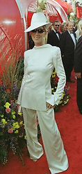 Canadian singer Celine Dion arrives at the Dorothy Chandler Pavilion in Los Angeles for the 71st annual Academy Oscar Awards, wearing a white Christian Dior backwards tuxedo and matching oversized fedora, with diamond-encrusted Raybans.