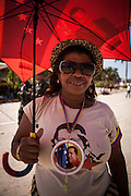 Chávez supporter holding a umbrella and a t-shirt with the image of the President of Venezuela Hugo Chávez during his funeral in Caracas, 8th March 2013. During Hugo Chávez funeral many people and stand sold miscellaneous articles that perpetuate Chávez presence. Everything from T-shirts, badges, earrings, baseball caps, sun glasses seemed suitable to have the President's image. The cult of Chávez is now more alive than ever.