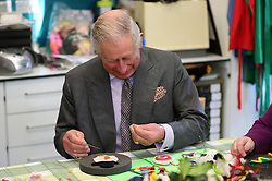 The Prince of Wales looks down at his finger after pricking it with a pin as he helps make Christmas decorations during a visit to the Sue Ryder Leckhampton Court Hospice near to Cheltenham in Gloucestershire, which he visits regularly and is celebrating 30 years of royal patronage.