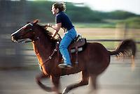 Barrel rider races her horse in practice, Indian Head Saskatchewan Canada
