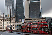Red London buses cross London Bridge with the City of London skyscrapers looming behind on 27th November 2019 in London, England, United Kingdom. This is a crucial route for city workers who cross this bridge towards the station, which is one of the busiest public transport hubs in the capital.
