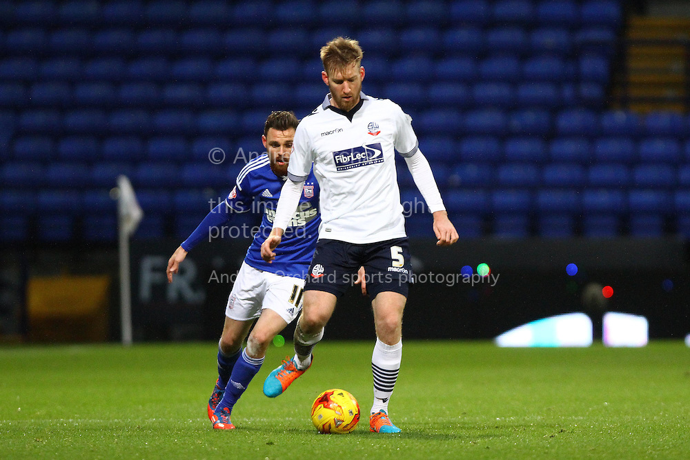 Tim Ream of Bolton Wanderers passes back under pressure from Paul Anderson of Ipswich Town. Skybet football league championship match, Bolton Wanderers v Ipswich Town at the Macron stadium in Bolton, Lancs on Saturday 13th December 2014.<br /> pic by Chris Stading, Andrew Orchard sports photography.