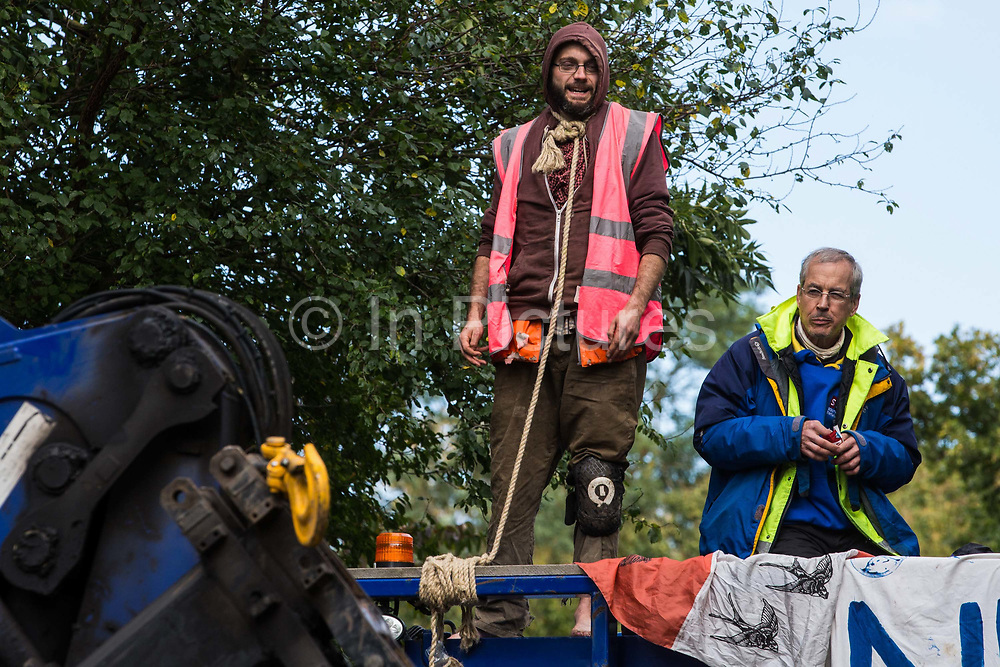 Two anti-HS2 activists, one of whom secured with a large rope around his neck, block a HGV used for works connected to the HS2 high-speed rail link on 28 September 2020 in Denham, United Kingdom. Environmental activists continue to try to prevent or delay works on the controversial £106bn project for which the construction phase was announced on 4th September from a series of protection camps based along the route of the line between London and Birmingham.