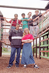 Multiracial group of children and teenagers standing on and around climbing frame in playground,