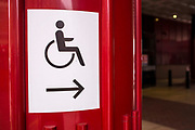 A sign showing the way for people with reduced mobility in the British Library in London, United Kingdom.  The signs use the International Symbol of Access designed in 1968. The symbol is often seen where access has been improved, particularly for wheelchair users, but also for other disability issues.  Frequently, the symbol denotes the removal of environmental barriers, such as steps, to help also older people, parents with baby carriages, and travelers.