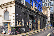 A back streest in Bloomsbury, London with an abandoned building with peeling paint and graffiti on the walls