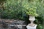 65821-00305 Iron fence on stone wall, Yellow lantana in container, Blue salvias.  Montrose Gardens Hillsborough, NC