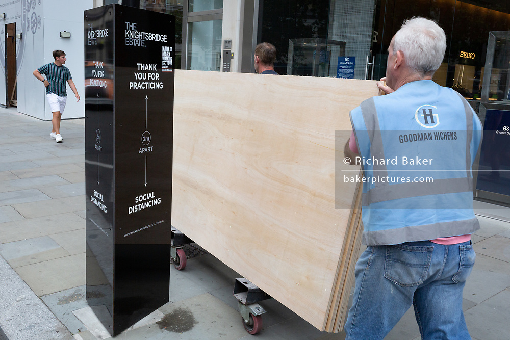 On the day that covid pandemic guidelines for shoppers in England mean that the wearing of face coverings in shops is mandatory, workmen carry construction plasterboard past social distancing  guidelines in Knightbridge, on 24th July 2020, in London, England.