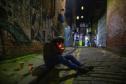 © Licensed to London News Pictures. 12/04/2021. Manchester, UK. A man sits on the pavement in an alley in the Northern Quarter to ensure his six friends can enjoy drinks at a nearby bar . People on a night out in Manchester City Centre as government restrictions to control the spread of Coronavirus are eased across the UK. Pubs, restaurants, hairdressers, gyms and non essential retailers are now permitted to serve customers within restrictions. Photo credit: Joel Goodman/LNP