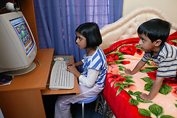 Brother and sister playing on the computer in bedroom,