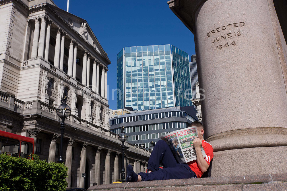 A Sun newspaper reader sits in the sunshine, below a statue in Threadneedle Street with the Bank of England to the left. We look upwards to the young man who wears a red shirt, all-typifying the Working Man in an English society still obsessed with class and status. This in front of the famous Bank of England in the City Of London, the financial district, otherwise known as the Square Mile. With such a wide-angle perspective the bank and its architecture looks powerful and influential in the UK's economy. There is a mixture of architectural eras here, with Sir John Soane's building legacy still a strong economic statement. The Sun is one of Britain's tabloid papers, selling over 3 million copies to mainly working class Britons, with a bias towards the young British male.