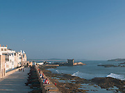 People gather at the ramparts of the old fortified walls of the medina at sunset in Essaouira, Morocco