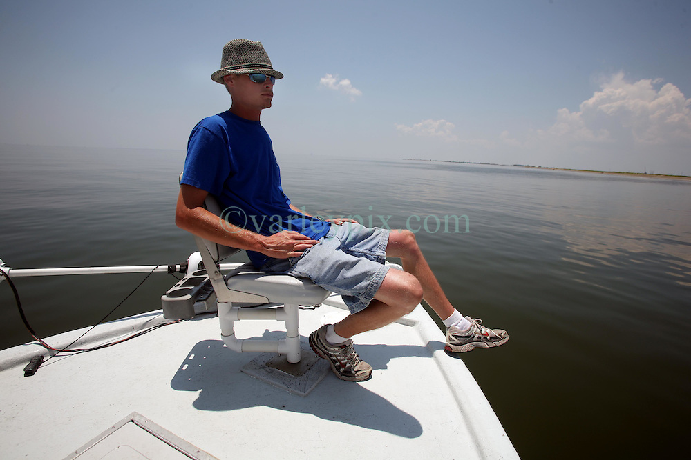 28 May 2010. Barataria Bay to Grand Isle, Jefferson/Lafourche Parish, Louisiana. <br /> Louisiana born and raised Justin Workmon studies the eerily empty ocean where water that would ordinarily be crystal clear but is now gravy coloured thanks to dispersed oil just off Grand Terre Island where Barataria Bay meets the Gulf of Mexico. Ordinarily the ocean would be filled with shrimp boats, sport fishermen, and sea birds, especially in the run up to memorial day weekend. The ecological and economic impact are devastating to the region. Oil from the Deepwater Horizon catastrophe is evading booms laid out to stop it thanks in part to the dispersants which means the oil travels at every depth of the Gulf and washes ashore wherever the current carries it. The Louisiana wetlands produce over 30% of America's seafood and are the most fertile of their kind in the world.<br /> Photo credit; Charlie Varley<br /> www.varleypix.com