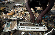A teenager pulls apart the contents of a computer keyboard monitors to recover a plate of metal that can be sold for money near the Agbogboloshie market in Accra, Ghana on Thursday August 21, 2008.