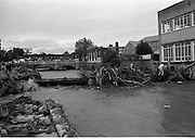 """Flooding at the Dodder..1986..26.08.1986..08.26.1986..28th August 1986..As a result of Hurricane Charly (Charlie) heavy overnight rainfall was the cause of severe flooding in the Donnybrook/Ballsbridge areas of Dublin. In a period of just 12 hours it was stated that 8 inches of rain had fallen. The Dodder,long regarded as a """"Flashy"""" river, burst its banks and caused great hardship to families in the 300 or so homes which were flooded. Council workers and the Fire Brigades did their best to try and alleviate some of the problems by removing debris and pumping out some of the homes affected..Note: """"Flashy"""" is a term given to a river which is prone to flooding as a result of heavy or sustained rainfall...With the threat of a high tide looming,picture shows workmen struggling to remove the debris from the watermain crossing the river at Ballsbridge,Dublin."""