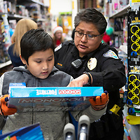 Niles Bahe, 9, and Detective Andrea Tsosie of the Gallup Police Department shop for a Monopoly game, Saturday Dec. 15, at Walmart in Gallup during Shop with a Cop.