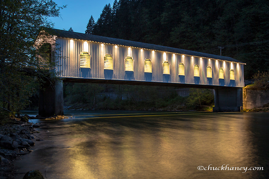 The Goodpasture Covered Bridge spans the McKenzie River at dusk in Lane County, Oregon, USA
