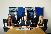 Corporate group shot featuring graduate recruits and company director taken in boardroom
