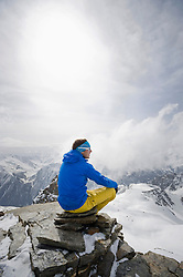 Man sitting contemplating mountain peak winter