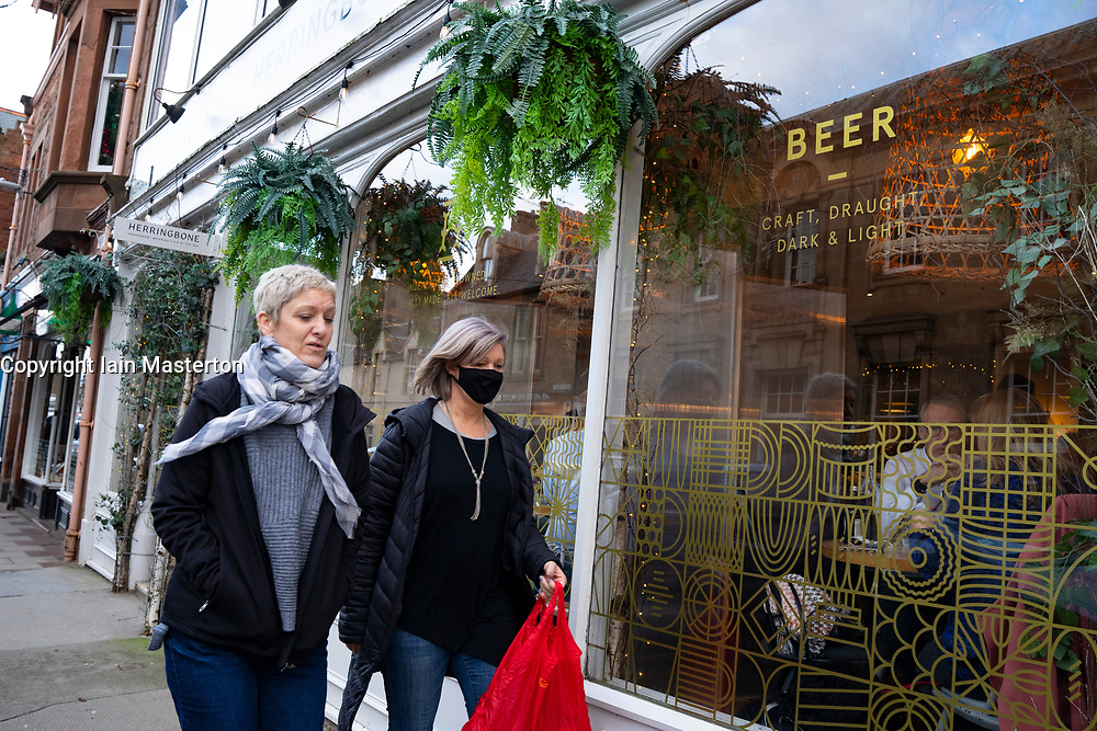 North Berwick, Scotland, UK. 17 December 2020. Scottish Government states that East Lothian is to move from level 2 to level 3 lockdown from Friday 18 December. This means restaurants and bars are not allowed to sell alcohol. Pic;  Women walk past The Herringbone bar and bistro in North Berwick.   Iain Masterton/Alamy Live News