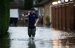 © Licensed to London News Pictures. 03/02/2021. Laleham, UK. A man wades through flood water on his way to work on a residential street in Laleham, Surrey which has flooded after the Thames broke it's banks. Large parts of the UK experience more wet conditions which is expected to bring further flooding. Photo credit: Ben Cawthra/LNP