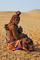 Portrait of young Himba woman in traditional dress with baby, Namibia, Africa. Fine art photography prints.
