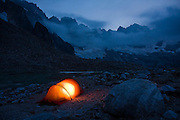 The peaks of the rugged Northern Picket Range tower over a tent glowing at twilight besides Luna Lake, North Cascades National Park, Washington.