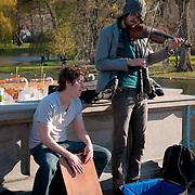 Street musicians play violin on Lagoon bridge of Boston Public Garden in spring 2011