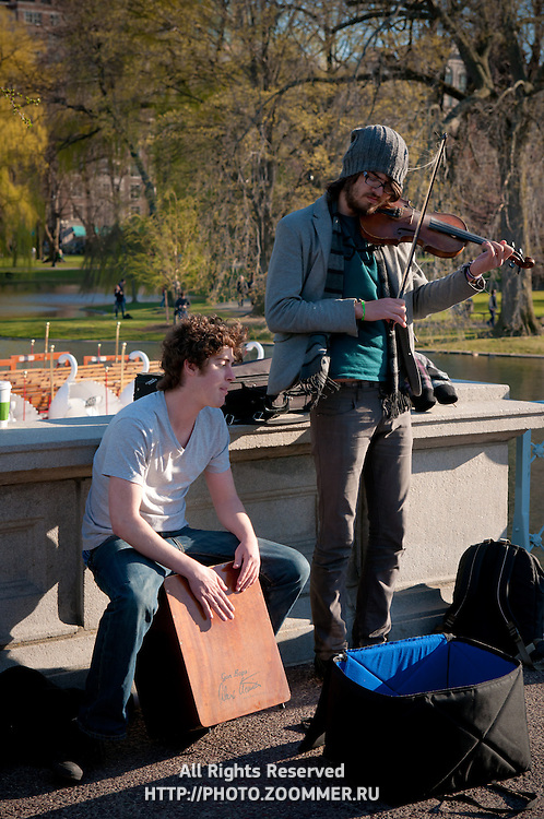 Street musicians play violin on Lagoon bridge of Boston Public Garden in spring 2011