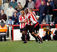 Photo: Leigh Quinnell.<br /> Brentford v Huddersfield Town. Coca Cola League 1. 21/01/2006. rentfords Dudley Campbell(L) and Andy Frampton(R) congratulate lloyd Owusu on his goal.