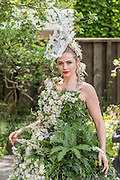 Laura, a model in a dress of 1500 real flowers on the M&G garden seranaded by a Royal Academy Cellist - The opening day of th Chelsea Flower Show.