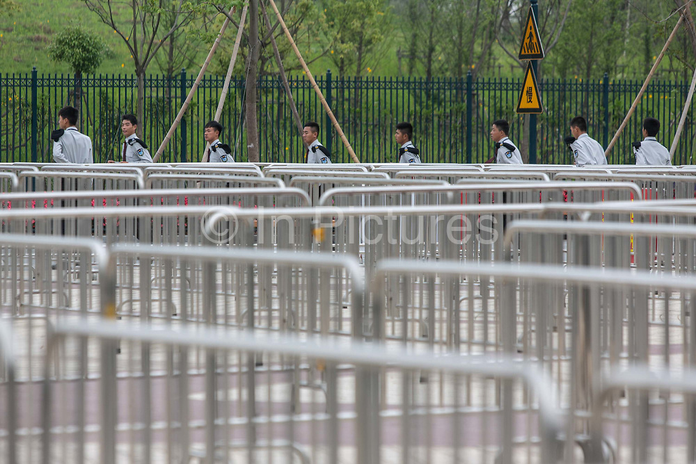 Security guards file past row upon rows of fencing in the Disneytown retail area of Walt Disney Co.s Disneyland Resort in Shanghai, China, on Saturday, May 7, 2016. The $5.5 billion Shanghai Disneyland is one  of the most profitable Disney ventures in the world and the first theme park on mainland China.