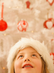 Close up of a girl in a furry Christmas hat looking up