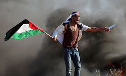 June 16, 2017 - Gaza City, Gaza Strip - A Palestinian protester waves a knife as he waves the national flag during clashes with IDF Israeli security forces following a protest near the border fence east of Jabalia refugee camp, against the blockade. (Credit Image: © Yasser Qudih/APA Images via ZUMA Wire)