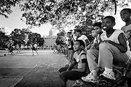 Children are watching and enjoying a local football game in the streets of Havana.