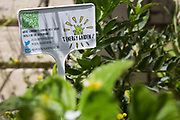 An energy garden sign at Brondebury Park train station 22nd May 2016,London,United Kingdom. At the meeting are local residents, Repowering London representatives and the station manager. Repowering London and their Energy Garden project in the making. Energy Gardens is a pan-London community garden project where reclaimed land alongside over ground train stations and track are cultivated by local community groups. Up 50 gardens are projected with the rail network being the connection grid. The project is a collaboration between Repowering London, local community groups and station managers working for TFL.