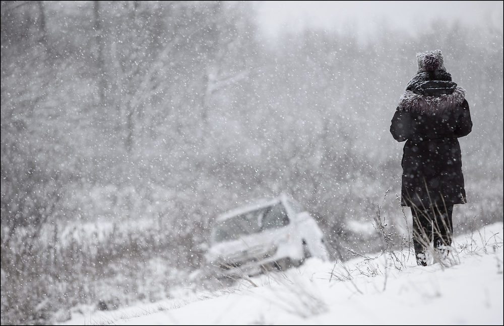 Emotional driver looking at her car after she slid into a ditch on Interstate 94 in Indiana.