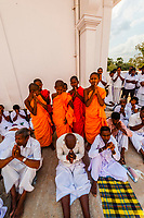 Novice Buddhist monks stand with praying pilgrims, Ruwanwelisaya Dagoba (Stupa) in the ancient city of Anuradhapura, Sri Lanka. Also known as the Ruwanweli Maha Seya, or Great Stupa is a sacred place of pilgrimage and worship in the ancient city of Anuradhapura.