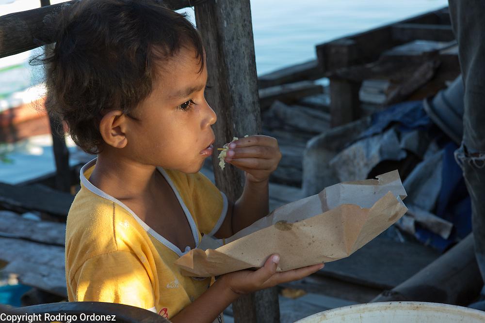 Umi, 5, eats. Her father Alwin Nurdin has just returned home from fishing overnight. They live in Kubur Cina, a neighbordhood of Lewoleba, Nubatukan subdistrict, Lembata district, East Nusa Tenggara province, Indonesia.